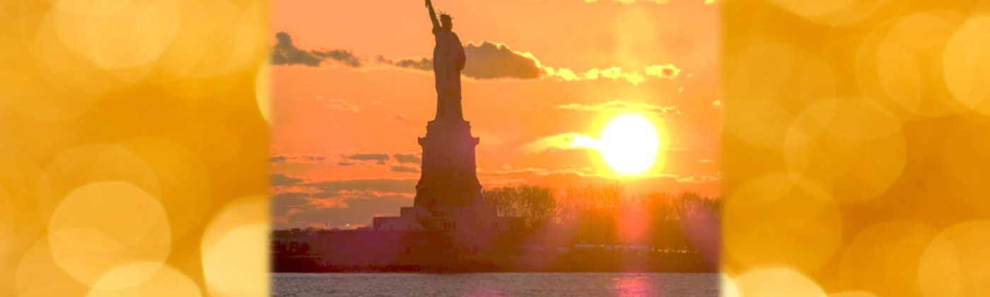 A picture of the statue of LIberty with a bright sun in the background.