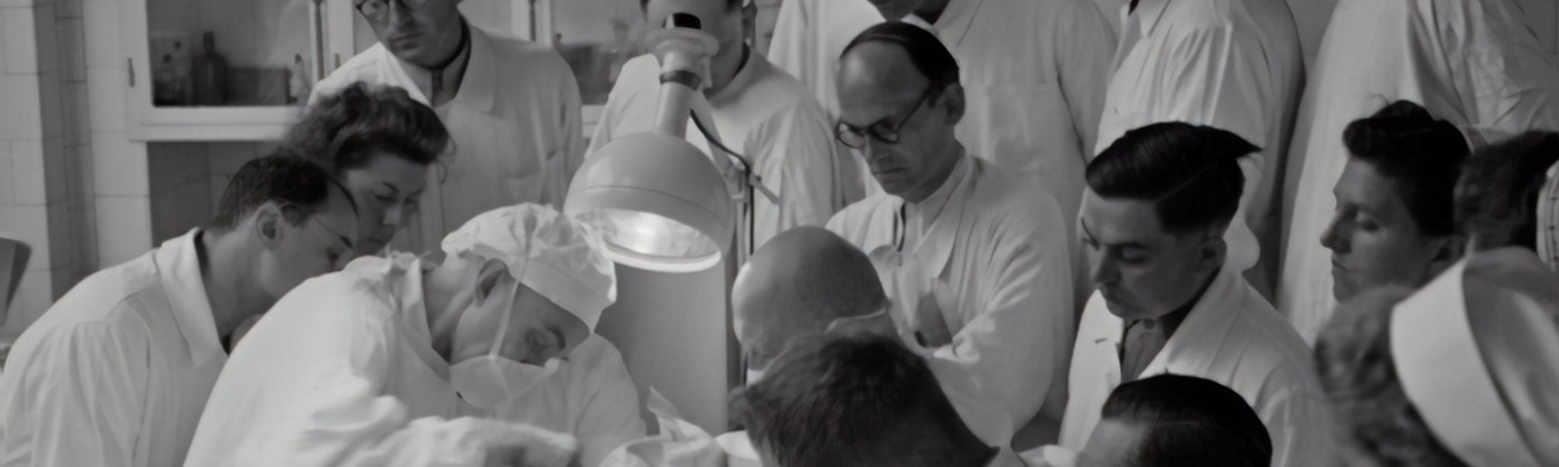 A black and white image of a bunch of males doctors in white coats peering over each other to witness a surgery of some kind.