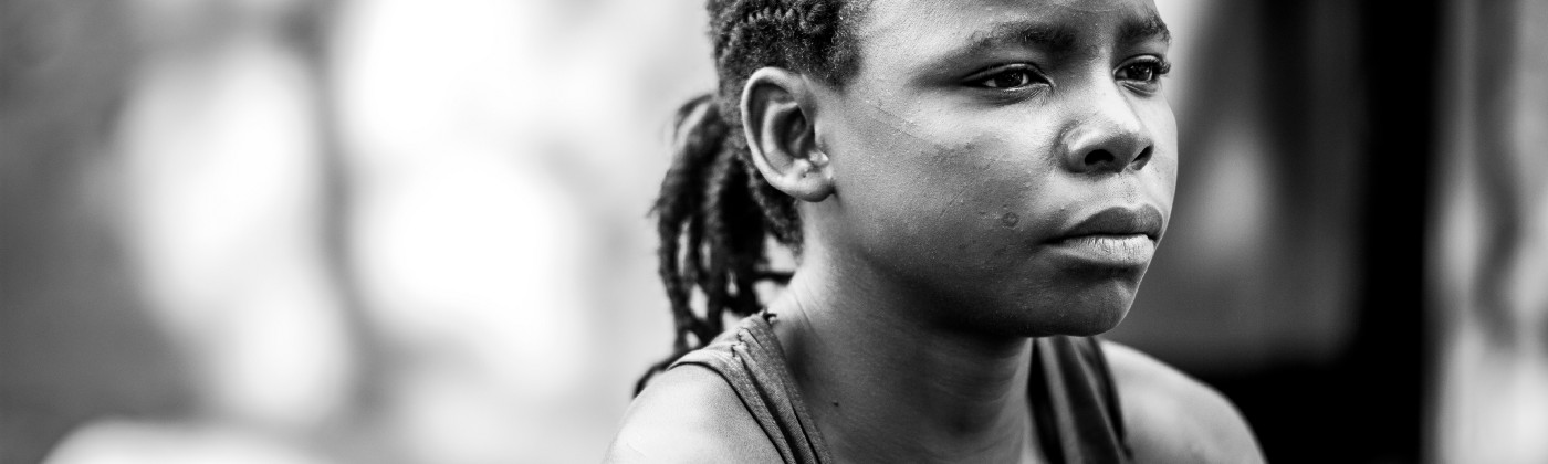 A young black girl is pictured in black and white. She has a pensive expression and is facing to the right.