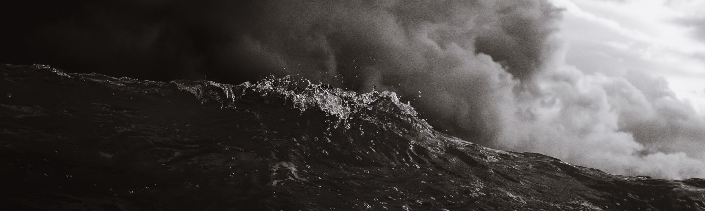 A wave cresting under a stormy sky