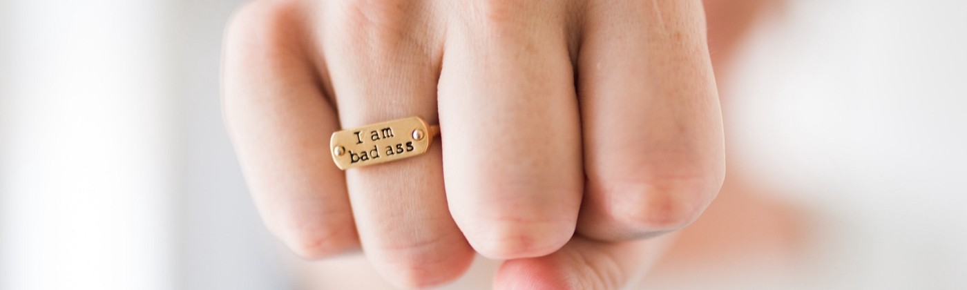 "Photo of a fist wearing a ring that says, ""I am badass."""