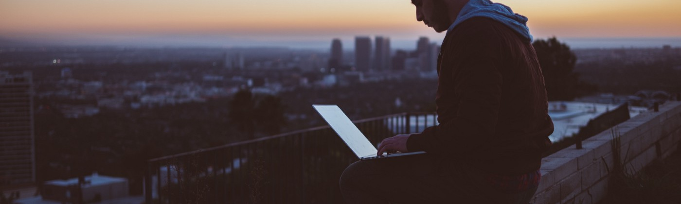Man sitting with laptop on a wall at sunrise