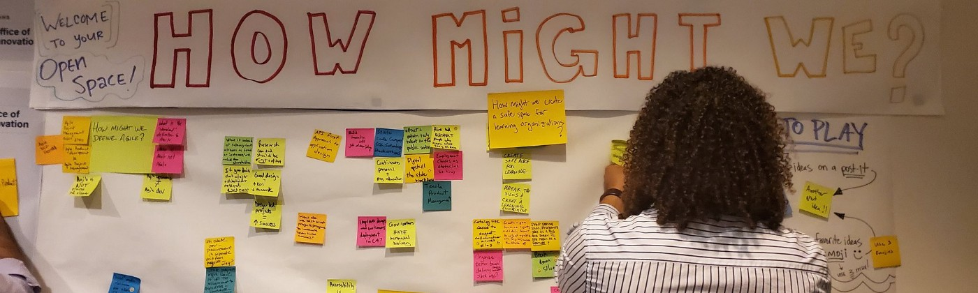 "A young man adding a sticky note to a wall full of ""how might we"" stickies."