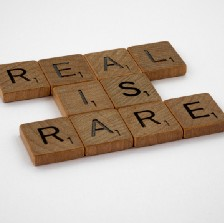 """Scrabble tiles spelling out """"real is rare."""""""