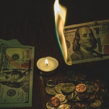 Burning hundred dollar bill with other bills, coins, and a candle on the table.