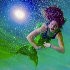 A woman wearing a mermaid fin and bathing suit is submerged in the sea bottom. The glowing round moon shines in the background surrounded by starts. The woman faces the viewer, her long and full red hair swaying towards the middle top of the frame. The woman looks happy.