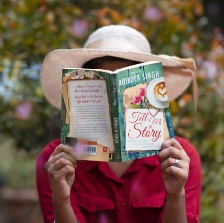 """A woman holds a book up in front of her face. The book title is """"Tell Me a Story. Woman is outside and wearing a sun hat."""