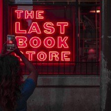 """Woman taking picture of sign that says, """"The last book store."""""""