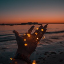 Hand sticking out of water, holding lights. Sunset in background.