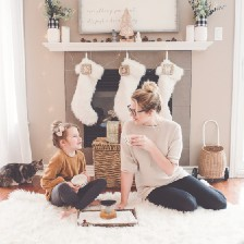 Mother and daughter sitting on floor drinking tea.