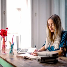 A female sits at their desk, writing in a journal with their laptop and pens nearby. #writing #journaling #writer