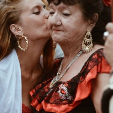 Younger woman kissing older woman on the cheek.