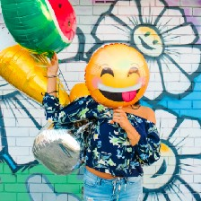 Person holding happy face ballon in front of their face.