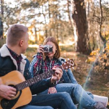 Man playing guitar on bench beside woman with camera taking his picture.