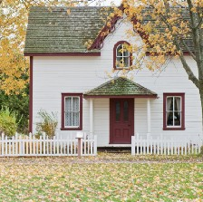 Small house with picket fence in autumn.