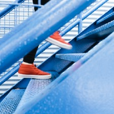 person in red sports shoes climbing a staircase