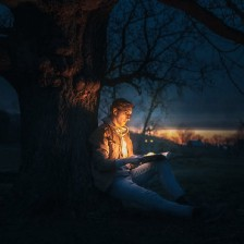 Man opening a magical book in the middle of a forest