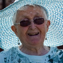 Elderly woman wearing hat and sunglasses.
