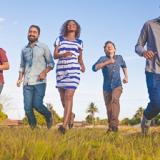 A group of smiling people walking through a field