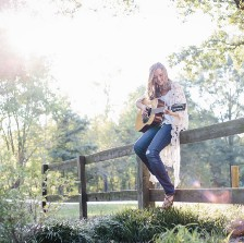 Woman sitting on fence playing guitar.