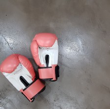 A pair of red and white boxing gloves sitting abandoned on a concerete floor