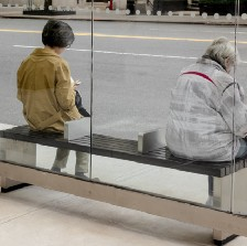Two women sitting at a bus stop with a spacer between them.