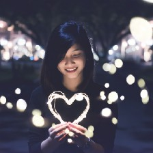 Woman holding heart outline, surrounded by lights.