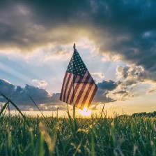 American flag in field with sunset sky.