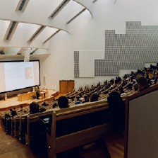 person lecturing in front of large screen in a lecture hall filled with students