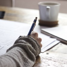 Picture of a hand that is holding a pen, writing on a blank sheet of paper, and a cup can be seen in the background.