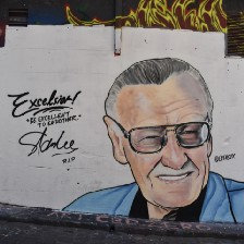 """Mural of Stan Lee with the words """"Excelsior, never give up!"""""""