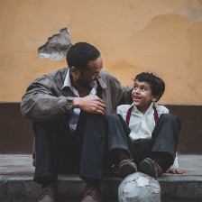 Father and son sitting together laughing.