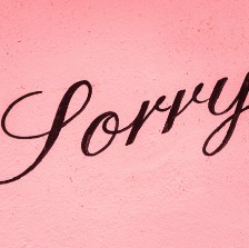 """""""Sorry"""" black type on pink background."""
