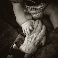 Old woman grabbing a baby's hand