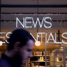 A man walking in front of a book store that says News Essentials on the sign.