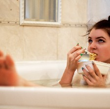 Woman in tub eating noodles.