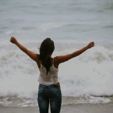 Back view of woman standing in front of ocean with arms outstretched.