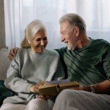 An old, healthy couple reading and smiling