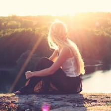 Woman sitting looking over lake with sunlight illuminating her head.