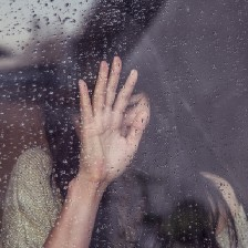 Crying woman with hand pressed against rainy window.