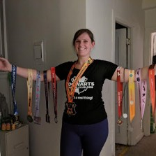 Amanda is wearing a Hogwarts Running Club t-shirt, her arms spread out and adorned with medals from virtual races