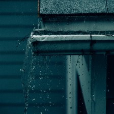 The leaf-filled gutter of a house as it rains.