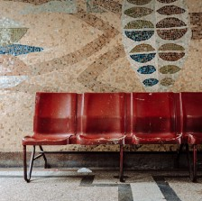Row of empty red chairs against a wall