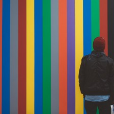Man faces rainbow colored striped wall