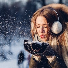 Woman in warm winter jacket with soft hood and earmuffs blows snow from her heavily mittened hands. Blurred snowy background. Feeling of hope and awe.