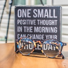 """Eyeglasses in front of plaque on a table that says, """"One small positive thought in the morning can change your whole day."""""""