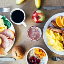 Two breakfast plates with eggs, sausage, ham, toast, and fruit.