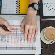 hands of man holding a pen and working on a financial report