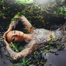 Beautiful woman is immersed in water on her back in seaweed. She is face up, eyes closed. Beautiful makeup, elbows bent, hands resting on the top of her head. Magic, beauty, fantasy aesthetic. Captivating.