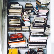 Stacks of old notebooks and journals in a cupboard.